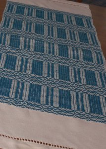 A finished cotton overshot table runner.